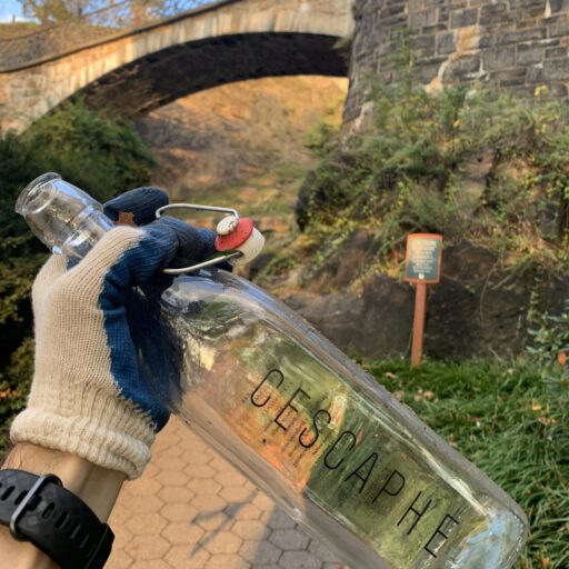A fancy littered clear water bottle with the name Cascaphe is shown held up by a work glove by a picturesque bridge scene in Philadelphia's Fairmount Park
